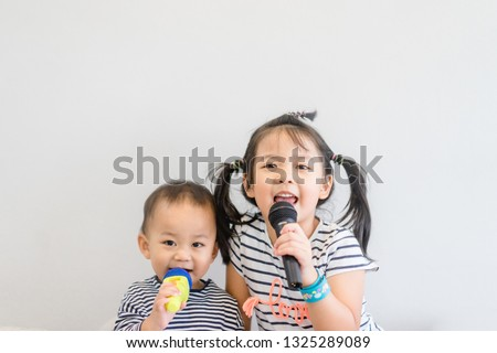 Little sister and her baby brother holding microphone and singing at art music school.Cute girl and baby boy relax learn to sing in music song class.Family with children and Art Education for Child.