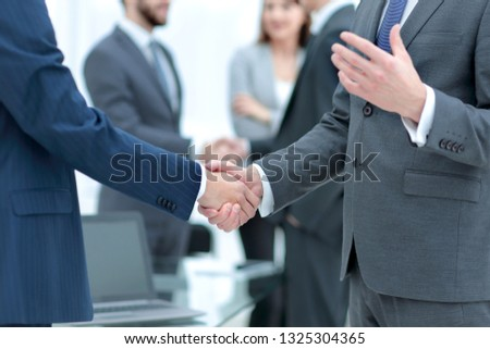 Business partners handshaking over business objects on workplace #1325304365
