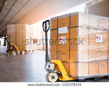 Hand pallet truck with stacked cardboard boxes wrapping plastic on pallet at warehouse dock. warehouse industry freight, logistics and shipment transport.  #1325378543