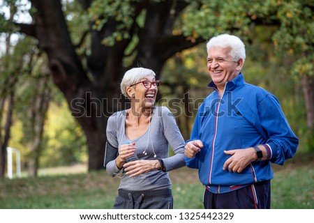 Mature couple jooging in the park and smile #1325442329