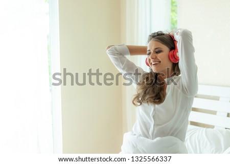 Lifestyle Beautiful cute girl woman feel happy enjoy listening to music with earphones headphones on white bedroom #1325566337