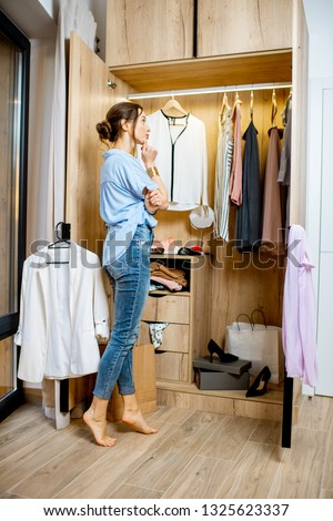 Young woman choosing clothes to wear, standing in the wardrobe at home #1325623337