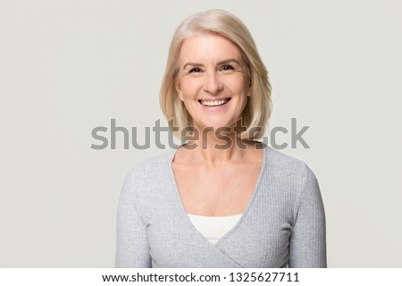 Smiling attractive casual middle aged mature beautiful woman looking at camera, happy healthy old senior lady with blond gray hair posing for portrait isolated on white grey blank studio background #1325627711