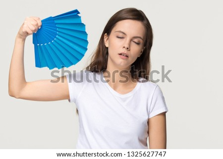 Tired young woman feel overheated suffering from heat stroke high temperature sweating problem, sweaty girl holding waving fan cooling in hot summer weather isolated on white grey studio background #1325627747