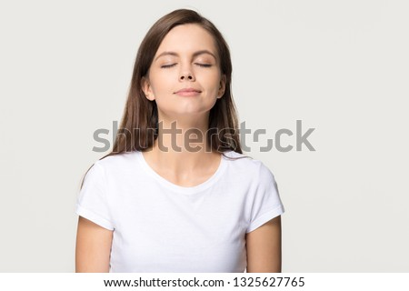 Happy calm teen girl enjoying good smell or pleasant fragrance, serene mindful young woman taking deep breath feel no stress free inhaling fresh air relaxing isolated on white grey studio background Royalty-Free Stock Photo #1325627765