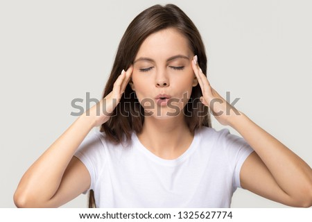 Stressed teen girl calming down relieving headache emotional stress relief, nervous young woman meditating massaging temples doing breathing exercises isolated on white grey studio blank background #1325627774