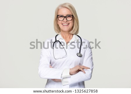 Happy mature middle aged woman doctor medical nurse portrait, smiling old senior female physician practitioner in uniform with stethoscope isolated on white grey studio background, healthcare concept Royalty-Free Stock Photo #1325627858