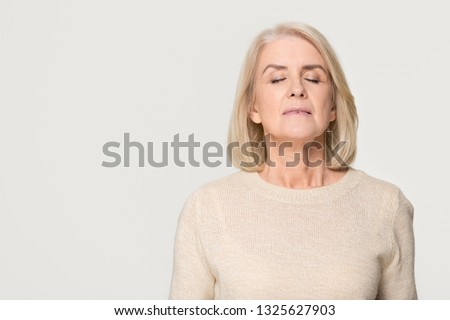 Calm tranquil mid aged old woman meditating breathing fresh air, serene mindful mature senior lady taking deep breath feeling no stress free relief harmony isolated on white grey studio background Royalty-Free Stock Photo #1325627903