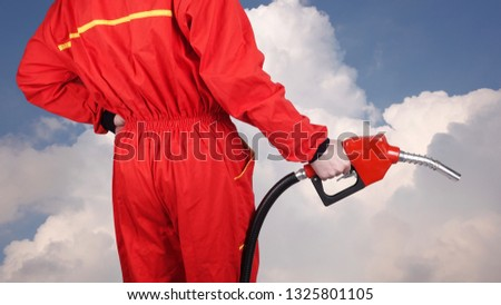 Man gas station staff  is holding red gasoline pistol pump fuel nozzle rear view from back  #1325801105