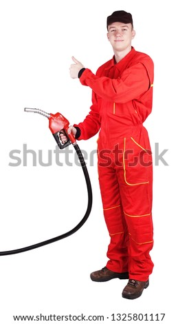 Man gas station staff  is holding red gasoline pistol pump fuel nozzle with thumb up sign gesture #1325801117