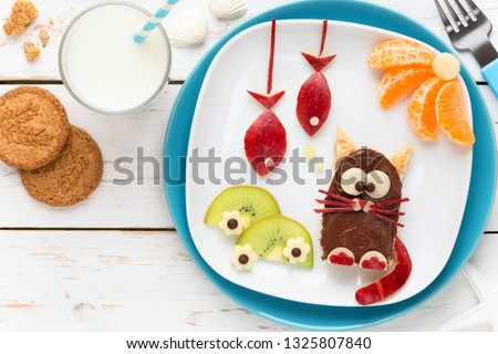 Fun Food for Kids - cute funny cat shaped toast covered with chocolate spread and decorated with fish shaped apple pieces, kiwi slices and tangerines #1325807840