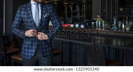 Man in expensive custom tailored suit standing and posing inside of a bar #1325905340