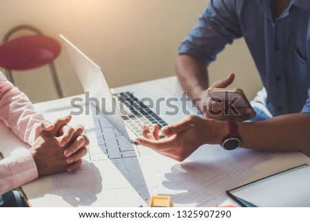 Architects or engineer construction discussing about interior design project with blueprints in architects workplace. Royalty-Free Stock Photo #1325907290