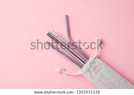 reusable stainless steel straws and cleaning brush in white cotton bag on pink background, eco friendly lifestyle #1325931128