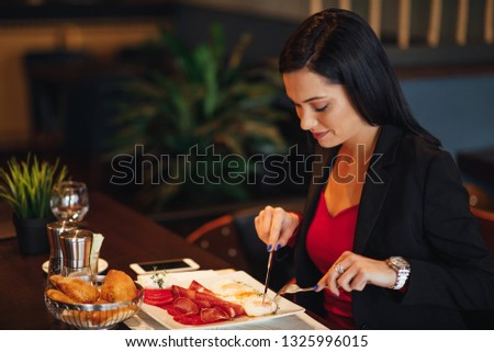 Young business woman on breakfast in a restaurant #1325996015