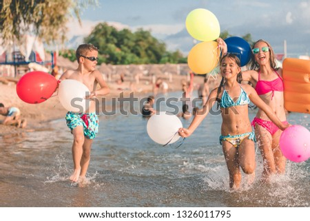 Happy kids running together with balloons through the water at the beach - Image #1326011795