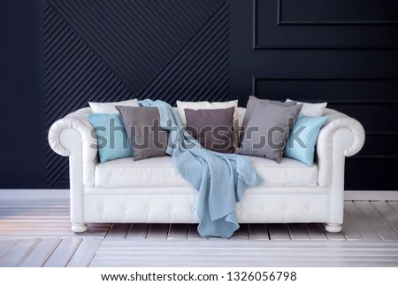 White coach with a grey and blue cushions and woolen blanket standing on a white wooden floor against dark blue wall. Minimalist interior design #1326056798