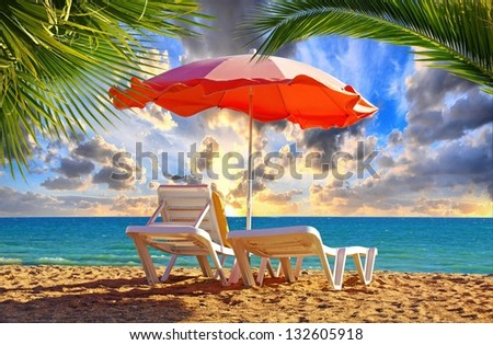 Beach chair and umbrella with palm trees on the beach / holiday feeling #132605918