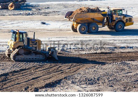 bulldozer and big truck at a construction site #1326087599