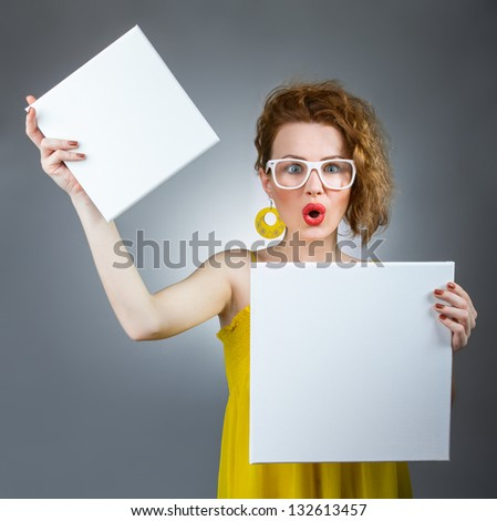 Surprised woman holding white board. Funny gilr with blank panel #132613457