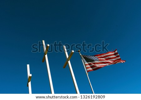American Flag Waving in the Wind next to three crosses Church