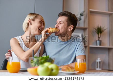 Young laughing girl feeding handsome man with croissant enjoying breakfast meal together  #1326196592