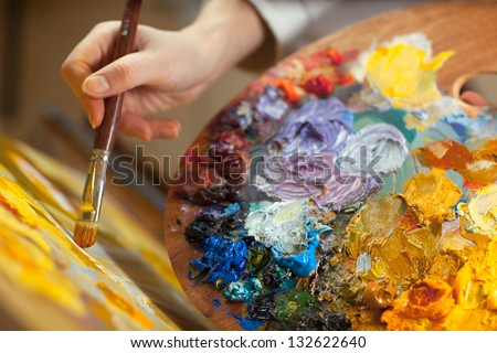 artist paints a picture of oil paint brush in hand with palette closeup Royalty-Free Stock Photo #132622640