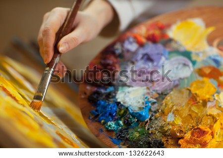 artist paints a picture of oil paint brush in hand with palette closeup #132622643