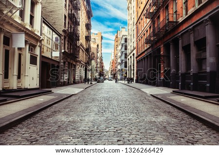 New York City old SoHo Downtown paving stone street with retail stores and luxury apartments #1326266429