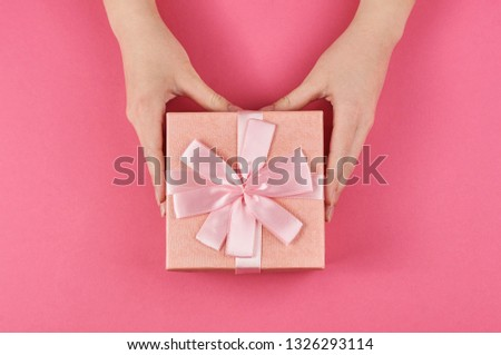 women's hands holding a pink gift box with a bow on a pink background view over the top                                #1326293114