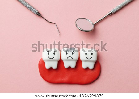 Healthy white teeth are smiling and tooth with caries is sad on pink background  and dentist tools mirror, hook. #1326299879