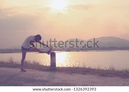 Young woman is warm up exercises front of the lake mountain on sunset time. #1326392393