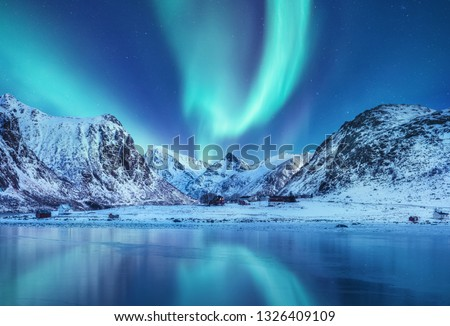 Aurora borealis on the Lofoten islands, Norway. Green northern lights above mountains. Night sky with polar lights. Night winter landscape with aurora and reflection on the water surface. Norway-image #1326409109