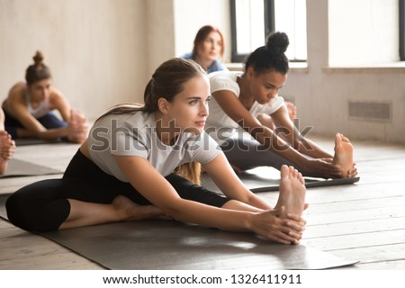 Group of diverse young sporty people practicing yoga lesson doing Head to Knee Forward Bend exercise, Janu Sirsasana pose, working out, indoor, mixed race students training at sport club or studio #1326411911