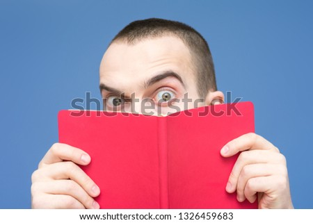 Male reads the book, stares in surprise at the camera, raise his eyebrows, facial expressions, close up, background, copy space, for advertising