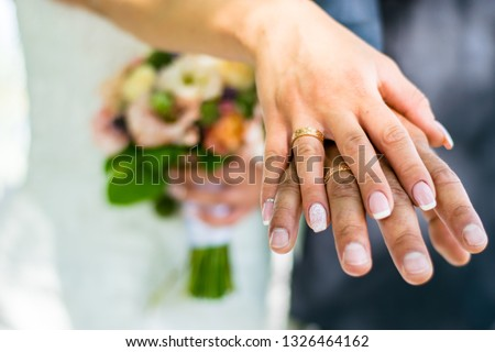 Newly weds holding hands and showing the rings #1326464162
