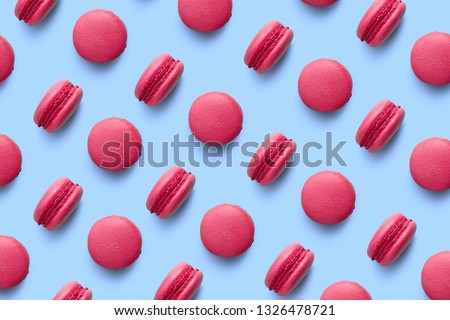 Macaroons on colored background, a pattern of colorful french cookies macarons. Beige, brown french cookies macarons on red background. Gift for Valentine's Day #1326478721