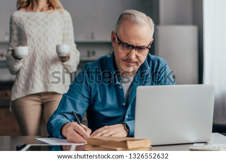 selective focus of concentrated man in glasses writing near laptop with wife holding cups on background #1326552632