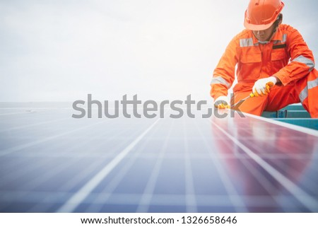 The male employee maintenance panels collect solar energy. Engineer working on checking and maintenance equipment at industry solar power. #1326658646