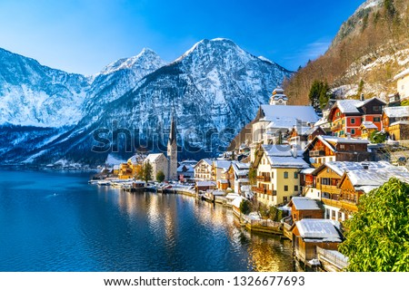 Classic postcard view of famous Hallstatt lakeside town in the Alps with traditional passenger ship on a beautiful cold sunny day with blue sky and clouds in winter, Salzkammergut region, Austria #1326677693