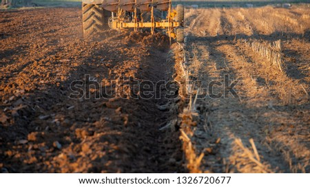 tractor while it is plowing the field #1326720677