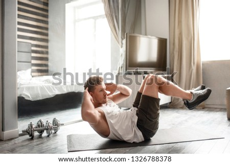Young well-built man go in for sports in apartment. He lying on carimate and does abs workout. Guy hold hands behind head. Intensive workout. #1326788378
