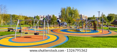 Panorama of colorful large playground in a city park. Empty modern outdoor playground in summer. Beautiful urban place for kids games and sport. Scenic view of children ground. Royalty-Free Stock Photo #1326795362