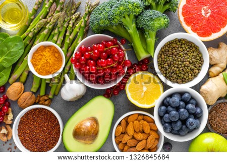 Healthy food background, spinach, quinoa, apple, blueberry, asparagus, turmeric, red currant, broccoli, mung bean, walnuts, grapefruit, ginger, avocado, almond, lemon, green peas and goji, top view #1326845684