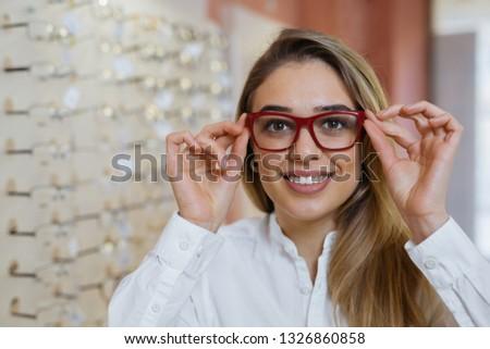 beautiful young woman choosing glasses in optic store. #1326860858