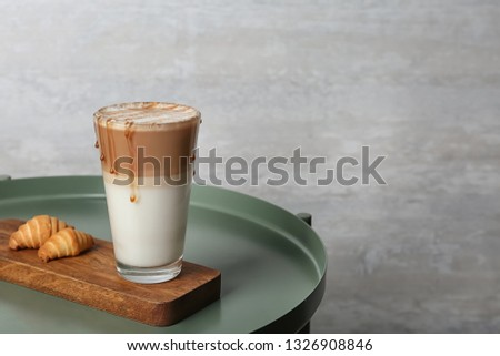Tray with glass of caramel macchiato and tasty pastry on table, space for text #1326908846