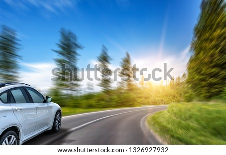 Car driving on highway surrounded by picturesque mountains. #1326927932