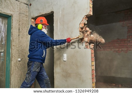 demolition work and rearrangement. worker with sledgehammer destroying wall Royalty-Free Stock Photo #1326949208