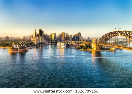 Arch of the Sydney Harbour bridge across Sydney harbour to The Rocks and Circular quay waterfront of city CBD lit by soft morning light between blue waters and sky. #1326989156