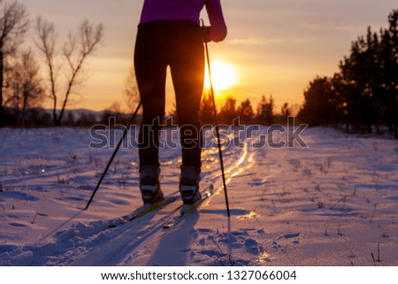 Defocused background, legs of a girl skier, against the backdrop of a sunset, concept of winter sports and outdoor activities. #1327066004